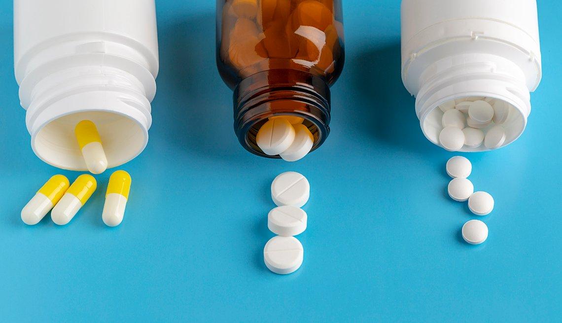 Tres frascos de medicamentos y diferentes pastillas