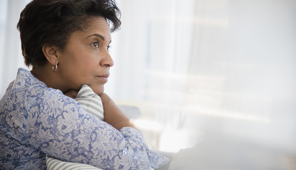Mature woman clutching pillow in front of the window