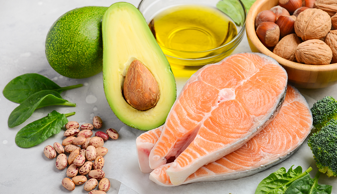 Selection of healthy food for heart, includes salmon, nuts, avocado and olive oil