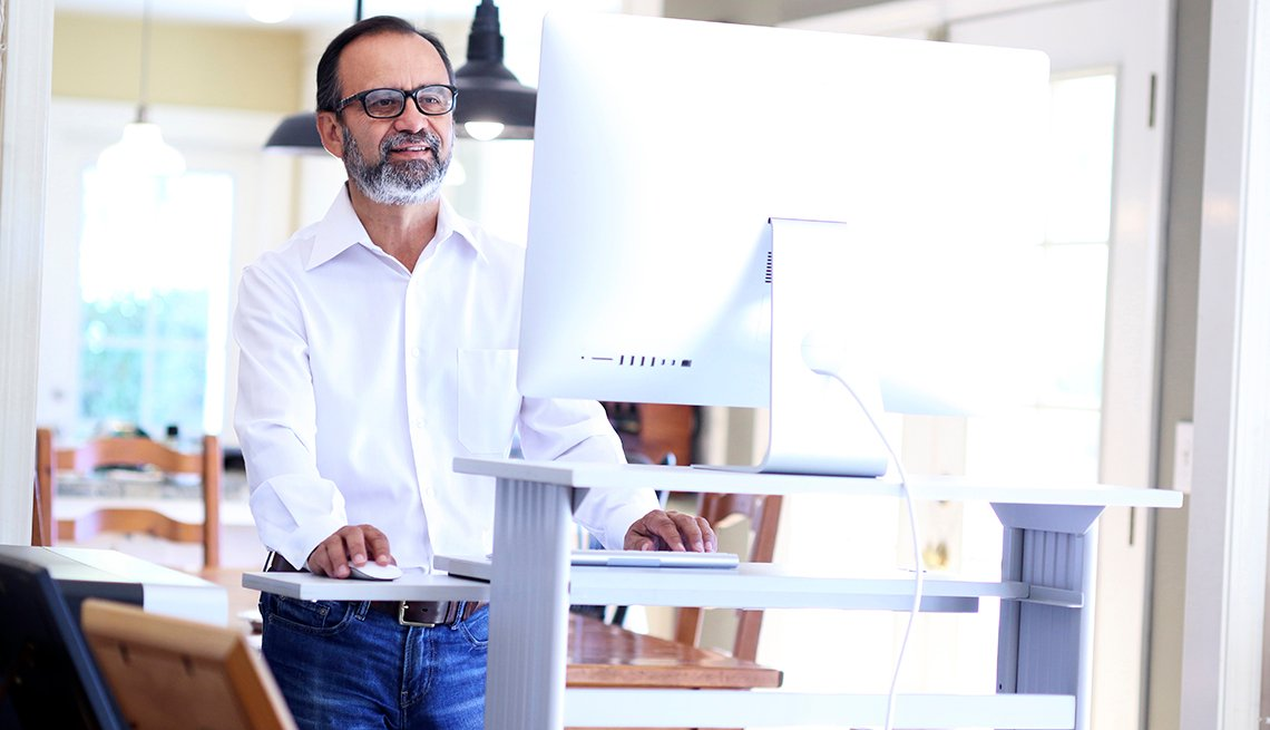 A businessman working at home stands at his standing desk as he leans forward and works on his computer.