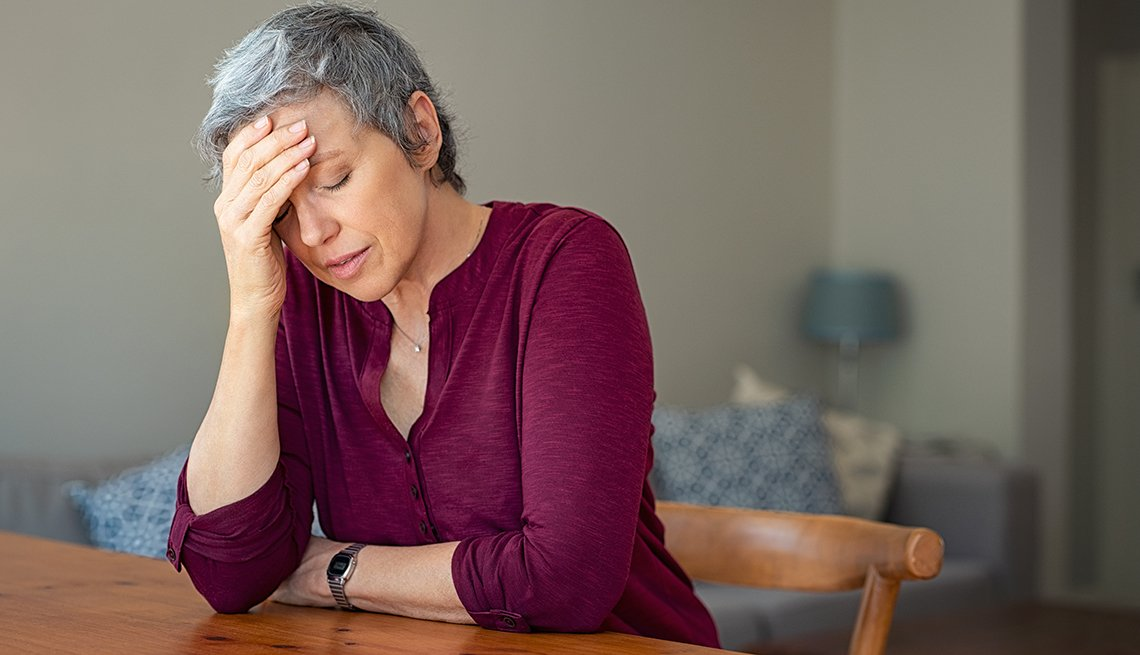 Senior woman suffering from headache and depressed while sitting at table in a living room.