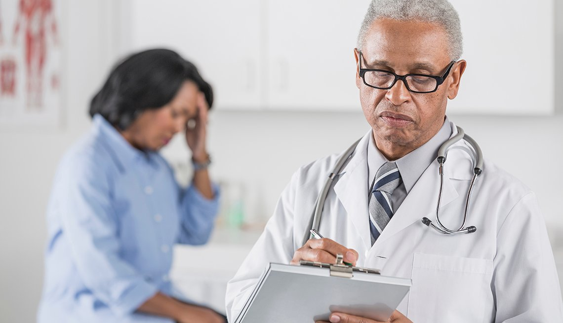 Male doctor writing on clipboard with patient suffering from a migraine in the backgroubnd.