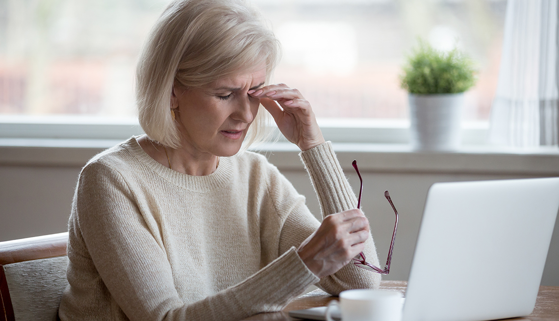 Mature woman rubs her irritated eyes after prolonged use of her computer