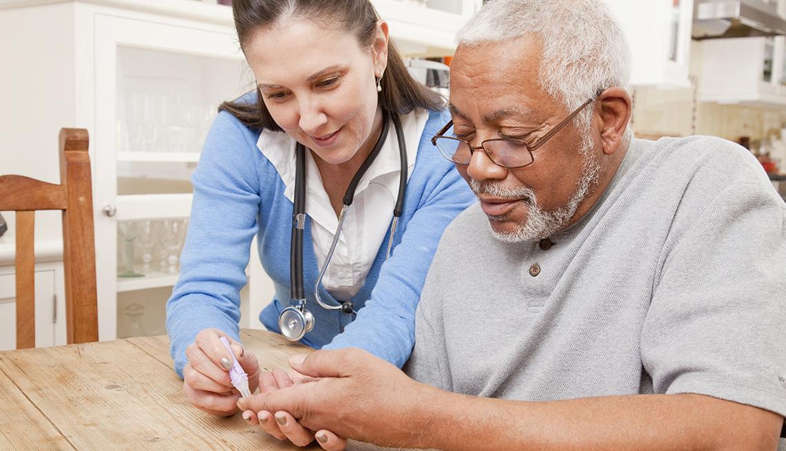 Enfermera hace prueba de azúcar a un paciente