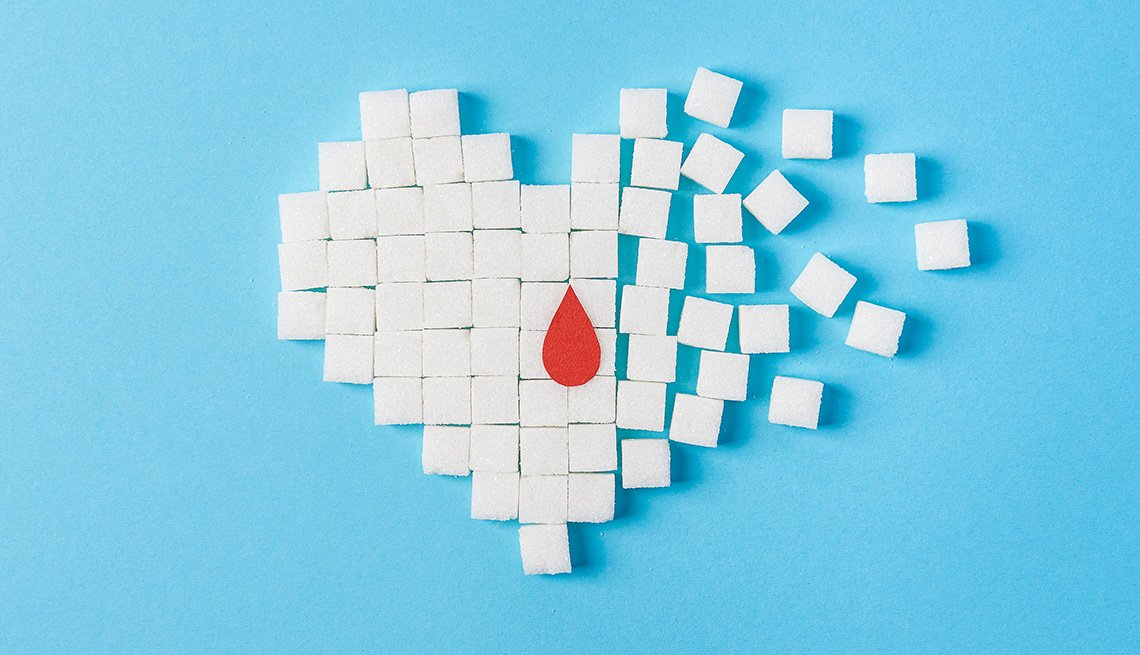 A drop of blood on a broken heart made of pure white cubes of sugar isolated on blue background.