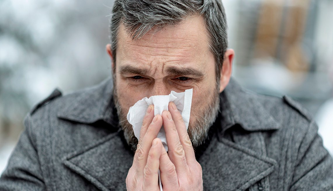A man with the flu blowing his nose while walking in the city square on a winter day.