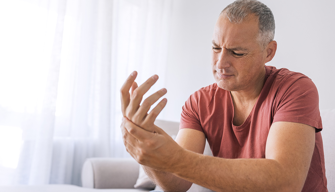 Mature man suffering from wrist pain at home while sitting on sofa during the day. Clenched painful hands