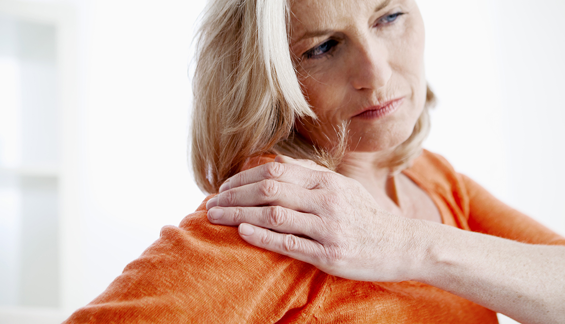 Woman massages shoulder while in pain