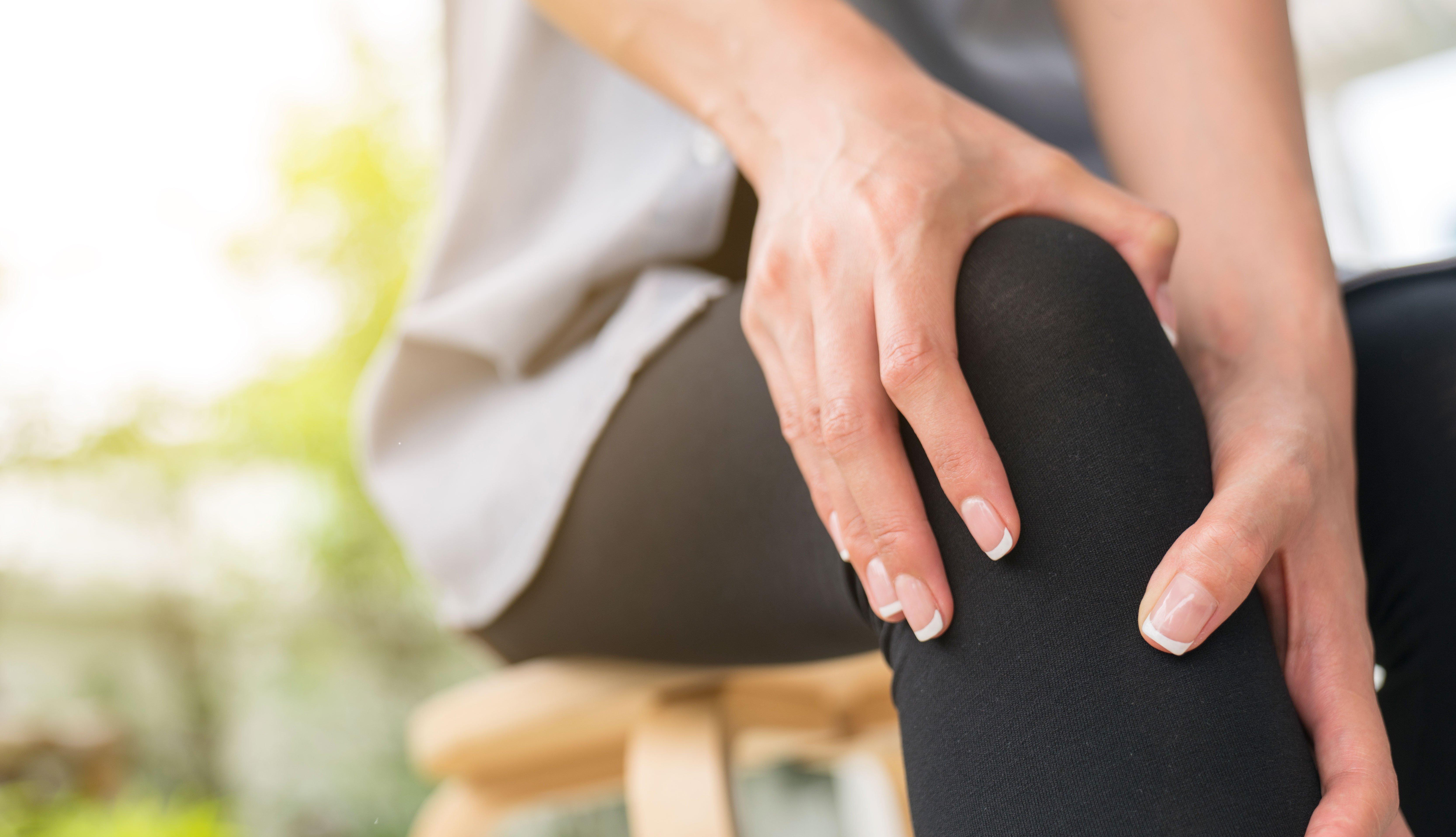 Mujer masajeando su rodilla