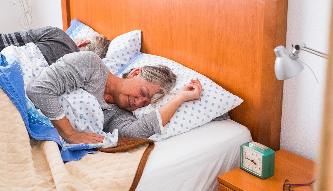 Mature couple sleeping, right before waking up. Woman looks stressed.
