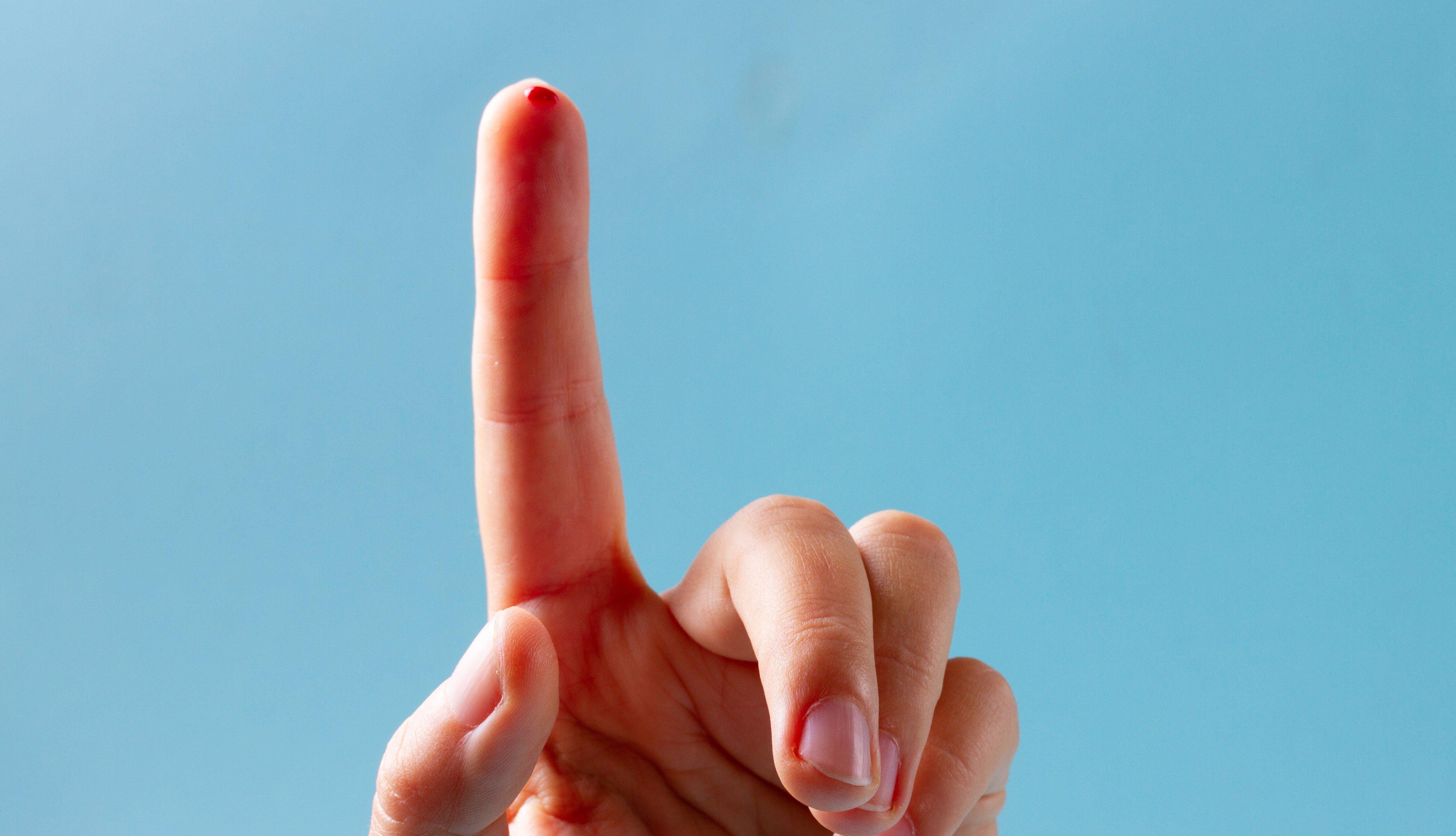 Dedo índice con un punto de sangre