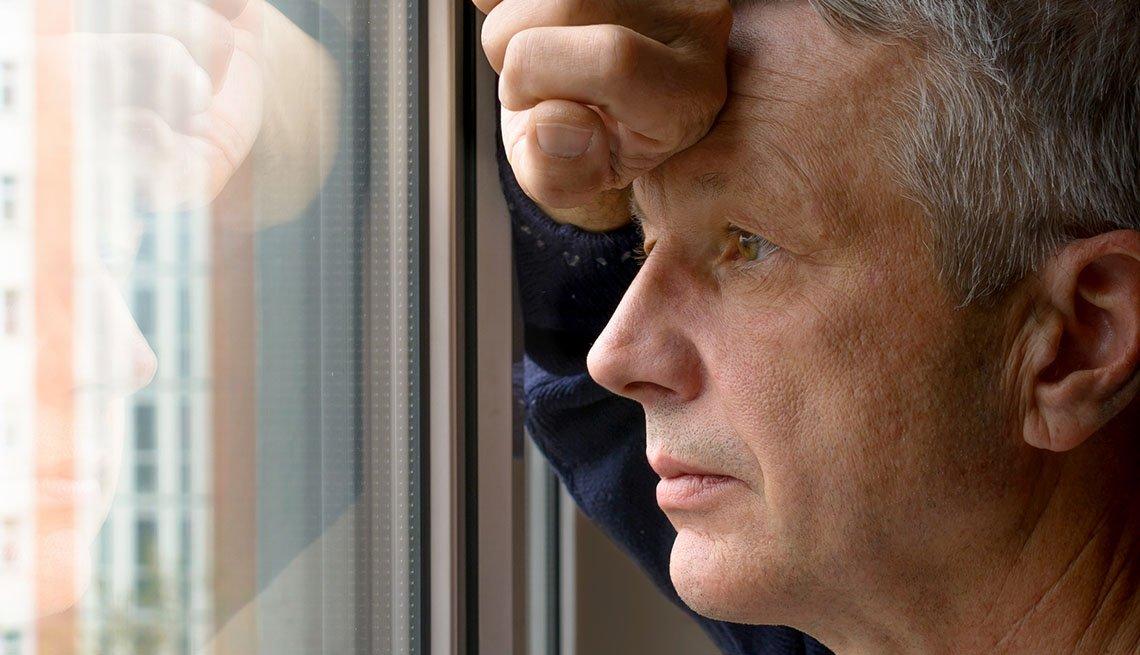 Hombre mira por una ventana