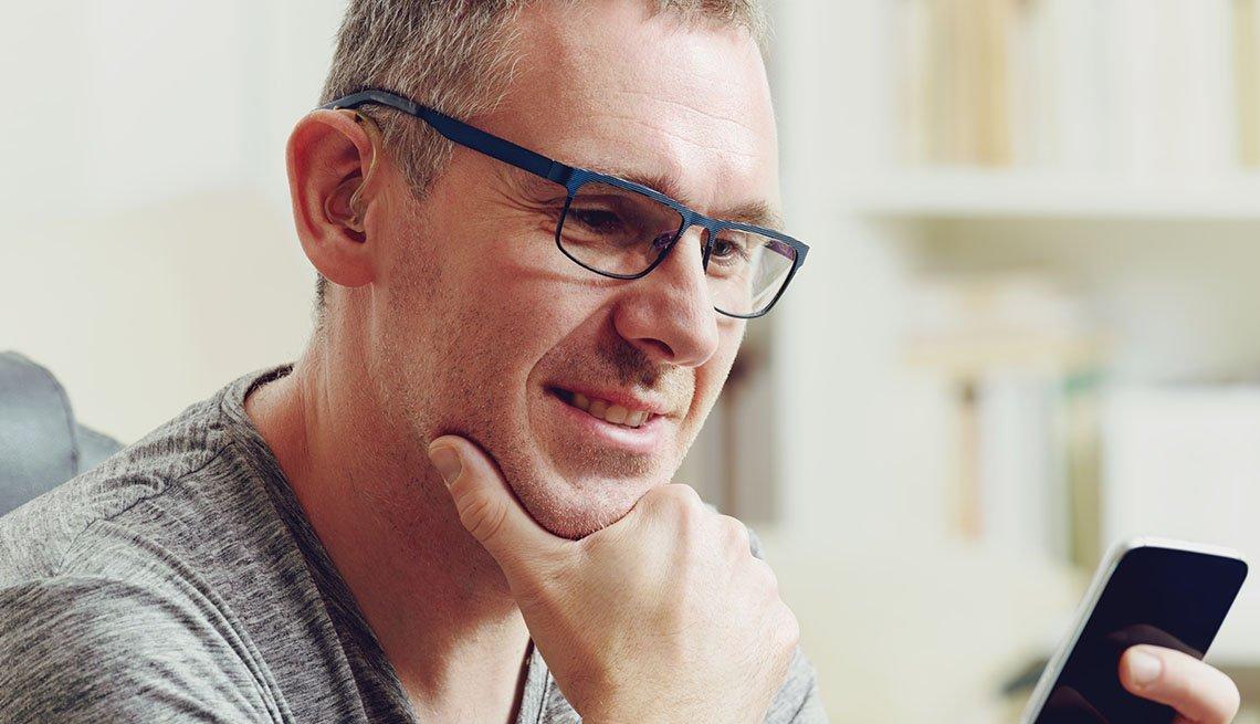 Hombre que usa audífonos para la sordera mira su teléfono