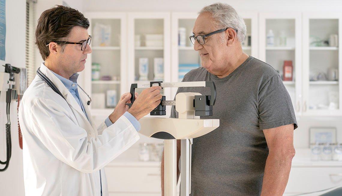 Médico pesando a su paciente