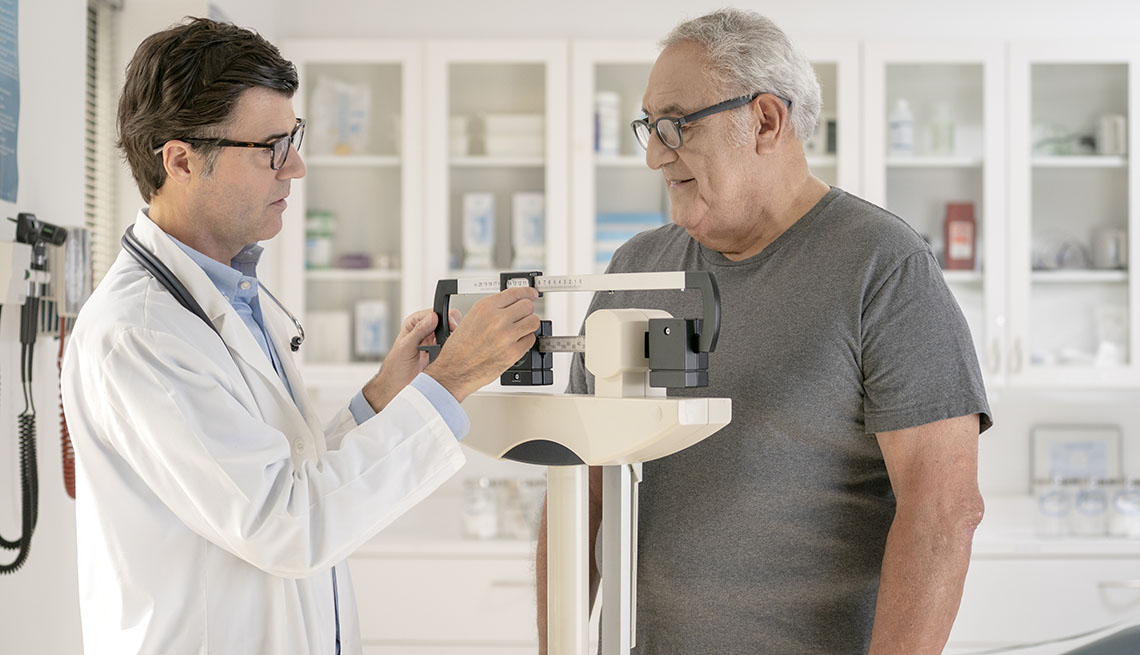Doctor weighs man on scale
