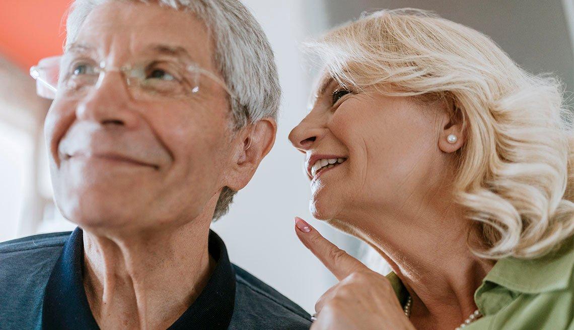Mujer le habla al oido a un hombre