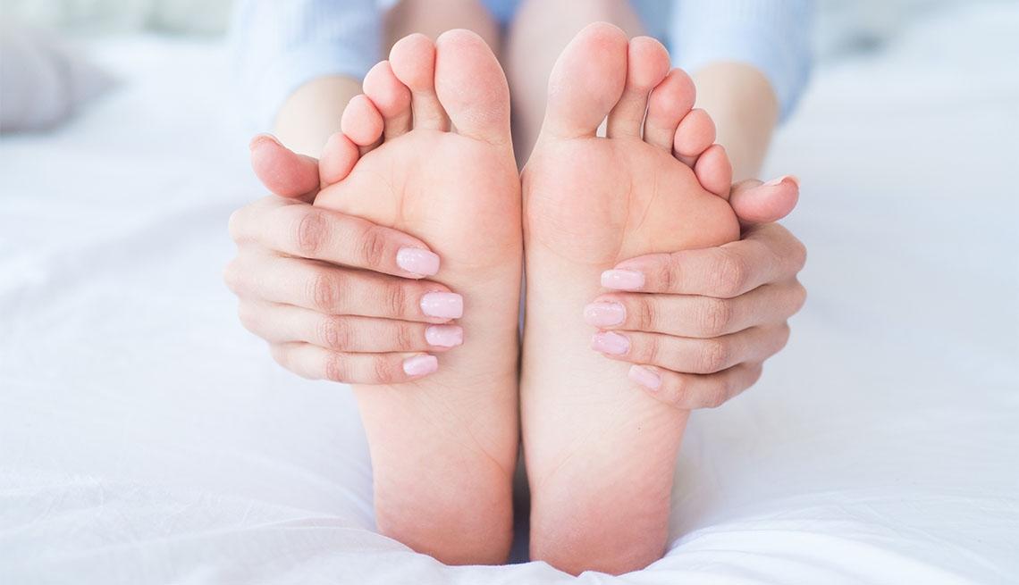Mujer agarrando sus pies