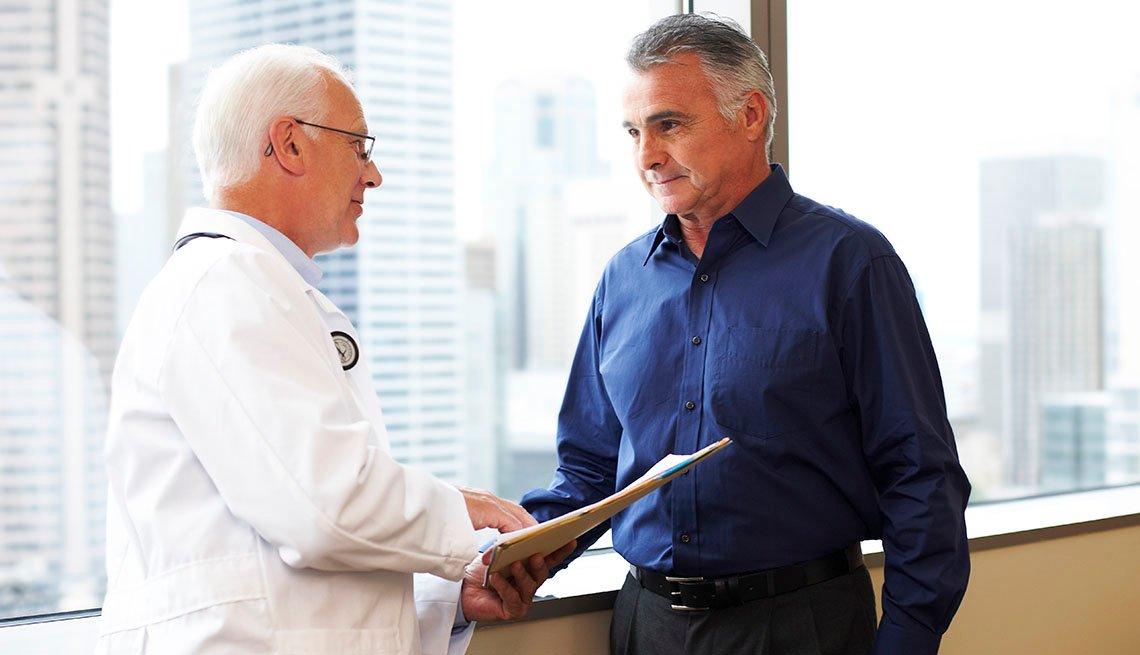 Doctor mira un informe médico con un paciente.