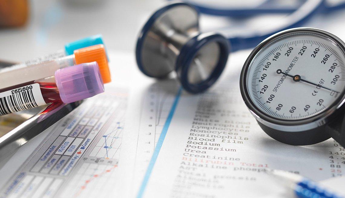 Escritorio de un médico con un estetoscopio, documentos y muestras de sangre