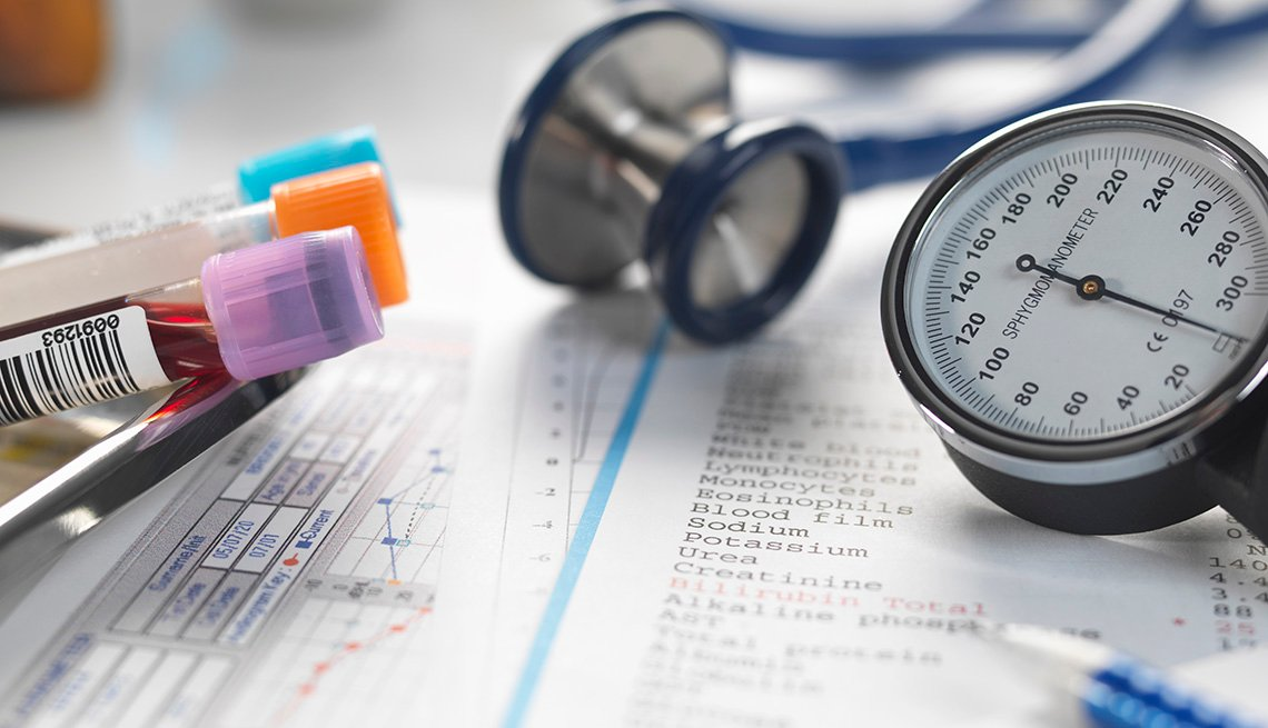 A doctor's desk filled with patient test results, samples, stethoscope and blood pressure gauge