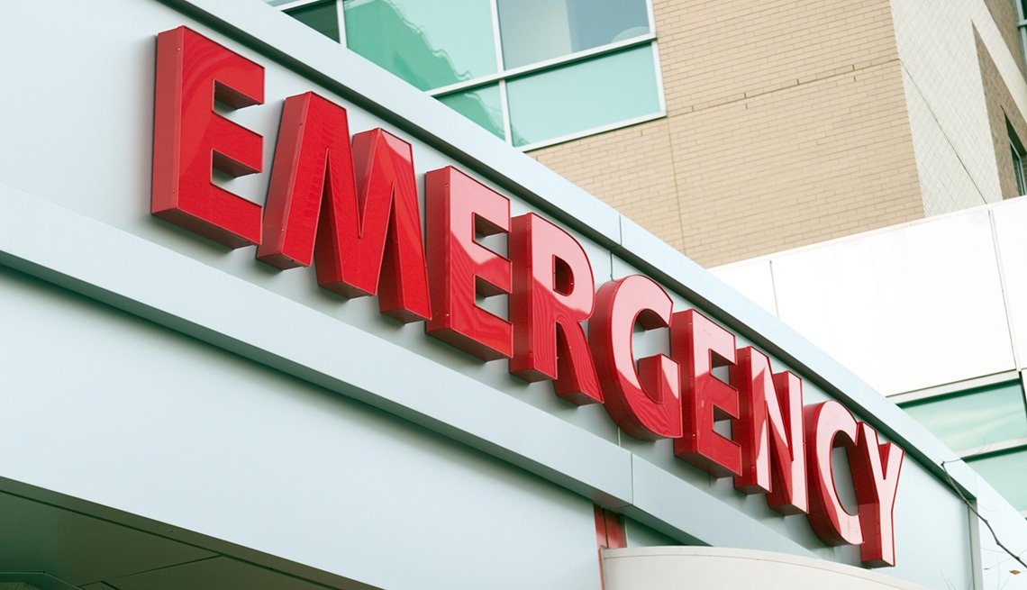 Rótulo color rojo que dice emergencia a la entrada de una sala de emergencias de un hospital