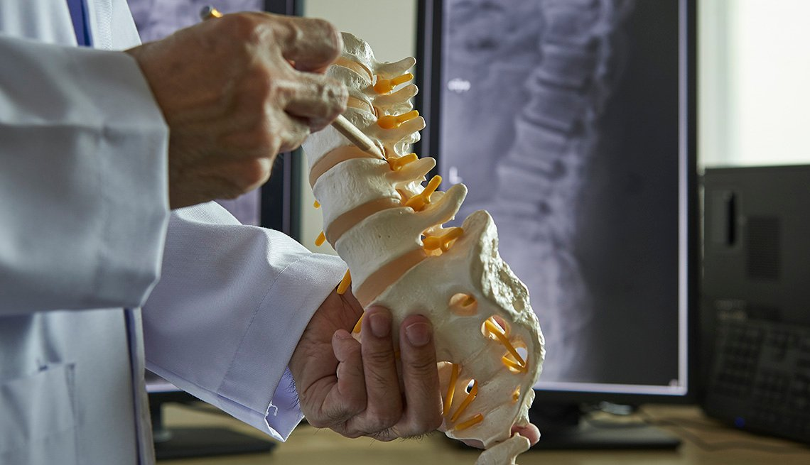 Un neurocirujano con un lápiz apuntando a un modelo de vértebra lumbar en un consultorio médico