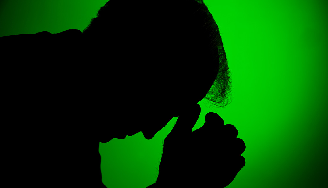A silhouette of a depressed man with his head down against a green background