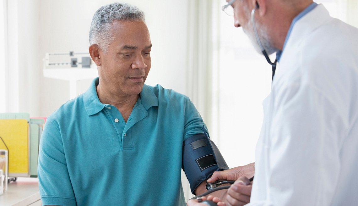 A doctor checks the blood pressure of male patient