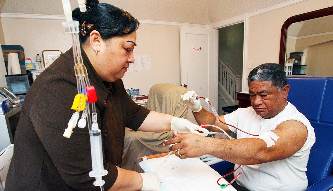 Una mujer ayuda a conectar la máquina de diálisis de un hombre en la sala de su hogar