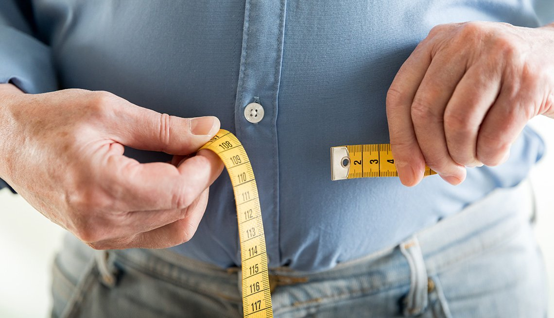 A man uses a tape measure to measure his stomach