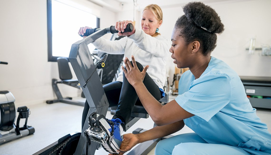 An occupational therapist helping a female patient use a static bicycle during physical therapy