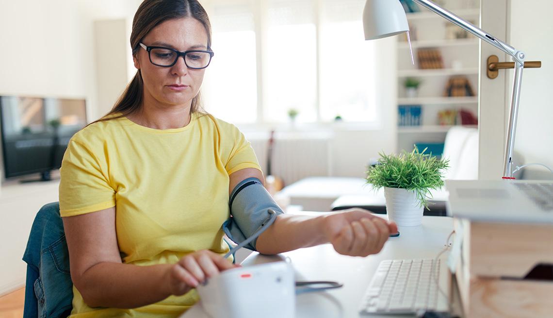 Una mujer monitorea su presión en casa