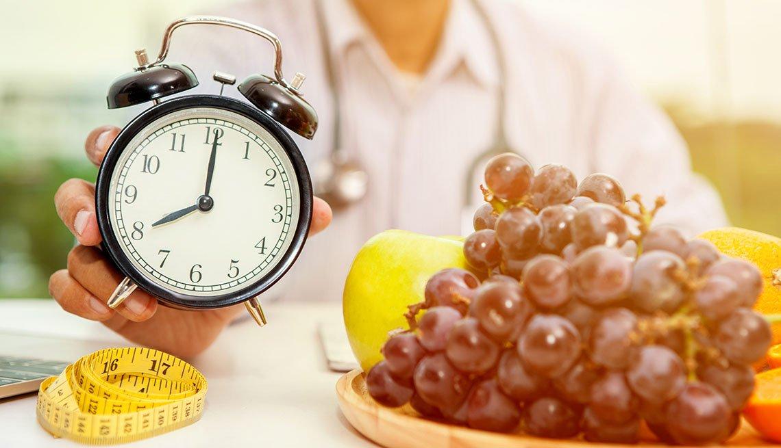 Una persona sostiene un reloj despertador y sobre una mesa hay uvas y una cinta de medir