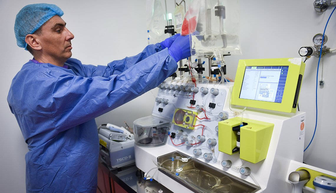 A lab technician handles an automated device used for cell processing