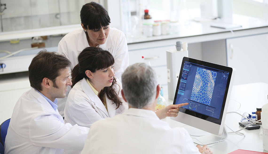 Cuatro científicos miran a una computadora