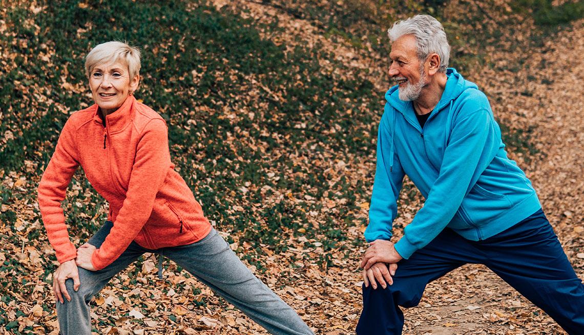 Una mujer y un hombre hacen ejercicios de estiramiento al aire libre