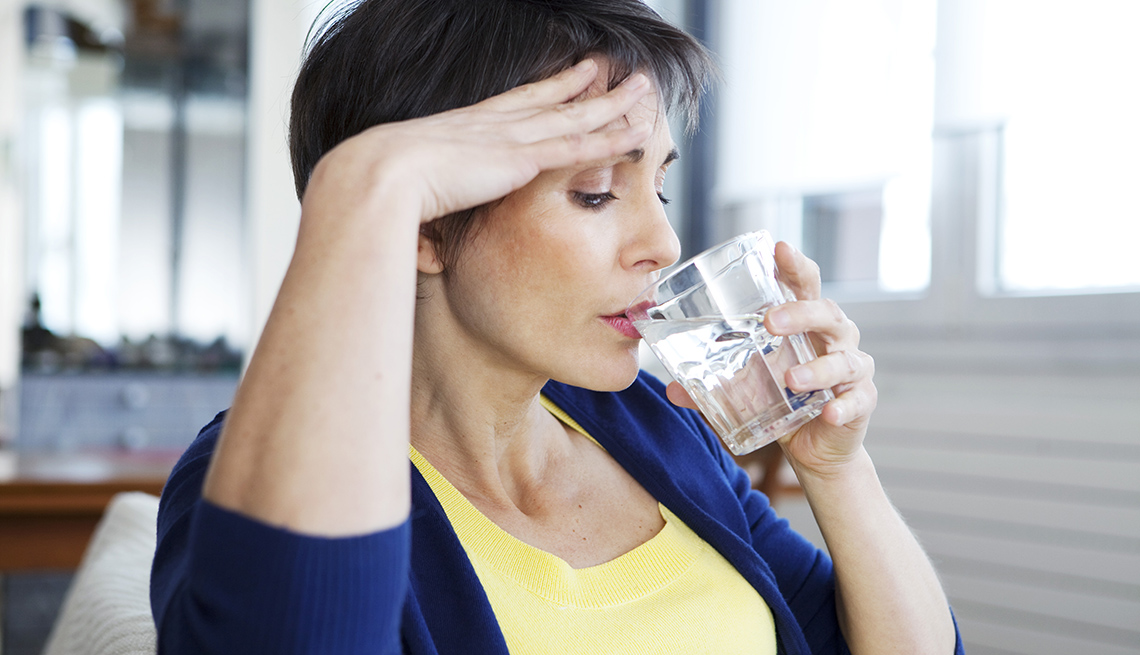 A woman experiencing hot flashes drinks water to cool down