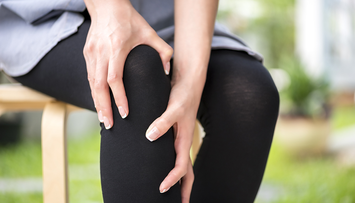 A woman clutching her knee suffering from pain in her knee