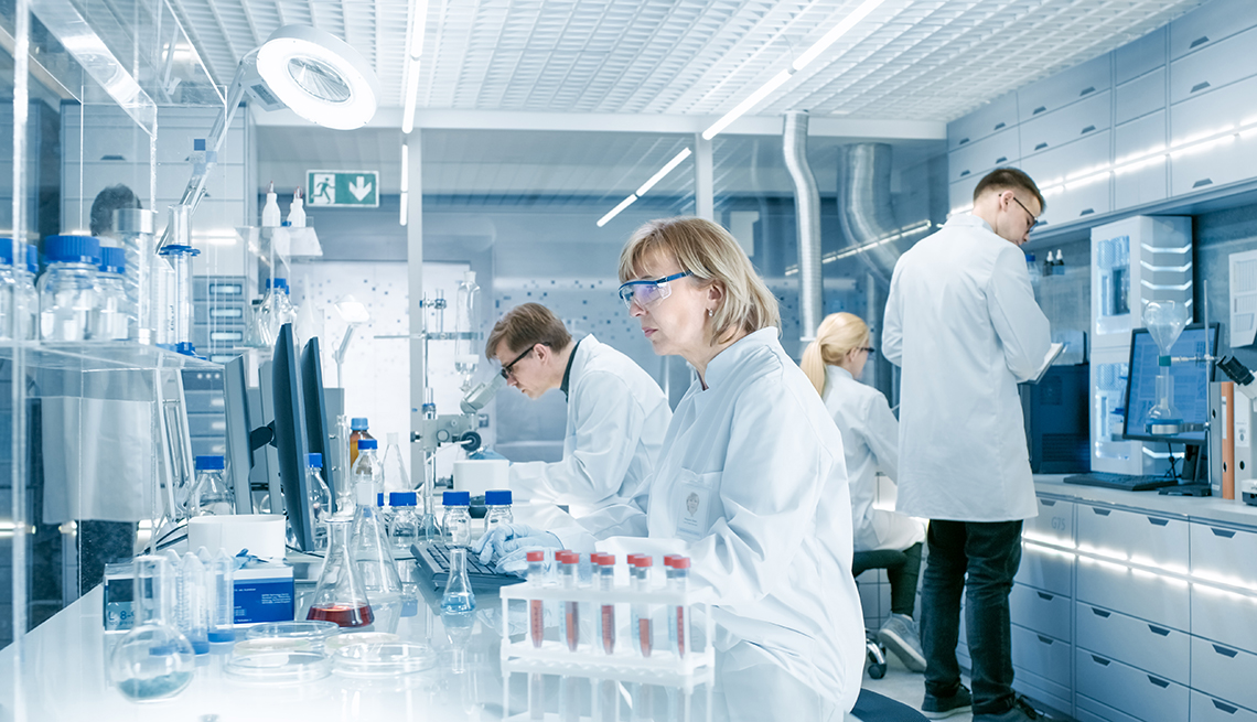 Four scientists working in a busy laboratory