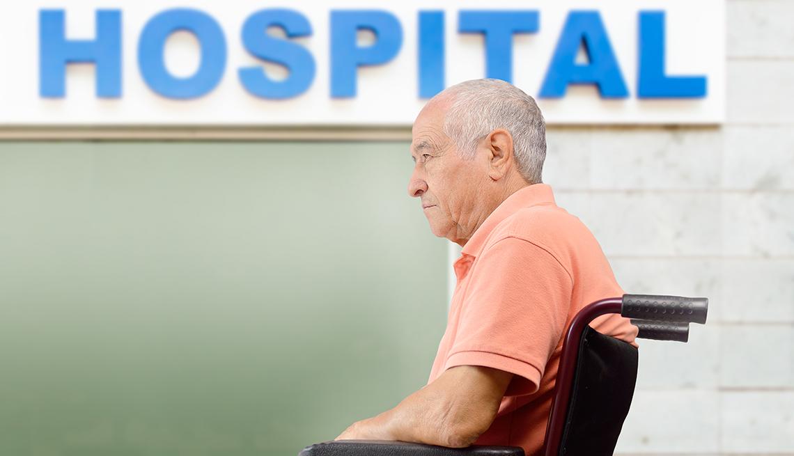 Hombre en sillón de ruedas frente a un hospital