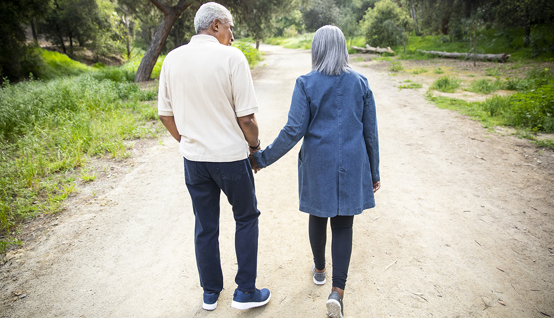 An older couple is walking down a path holding hands