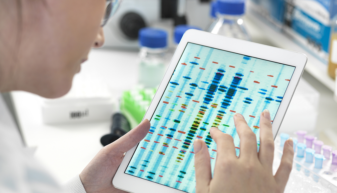 A scientist examining DNA sequence results on a digital tablet in a laboratory
