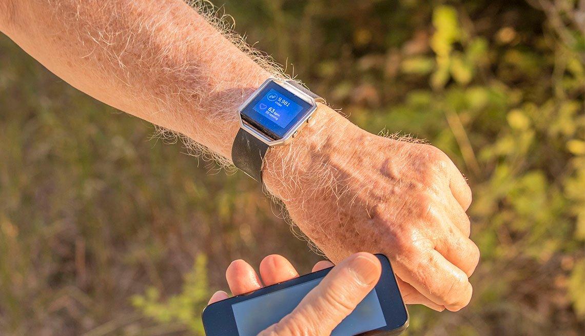 Hombre compara su reloj con su celular para verificar cuantos pasos ha dado
