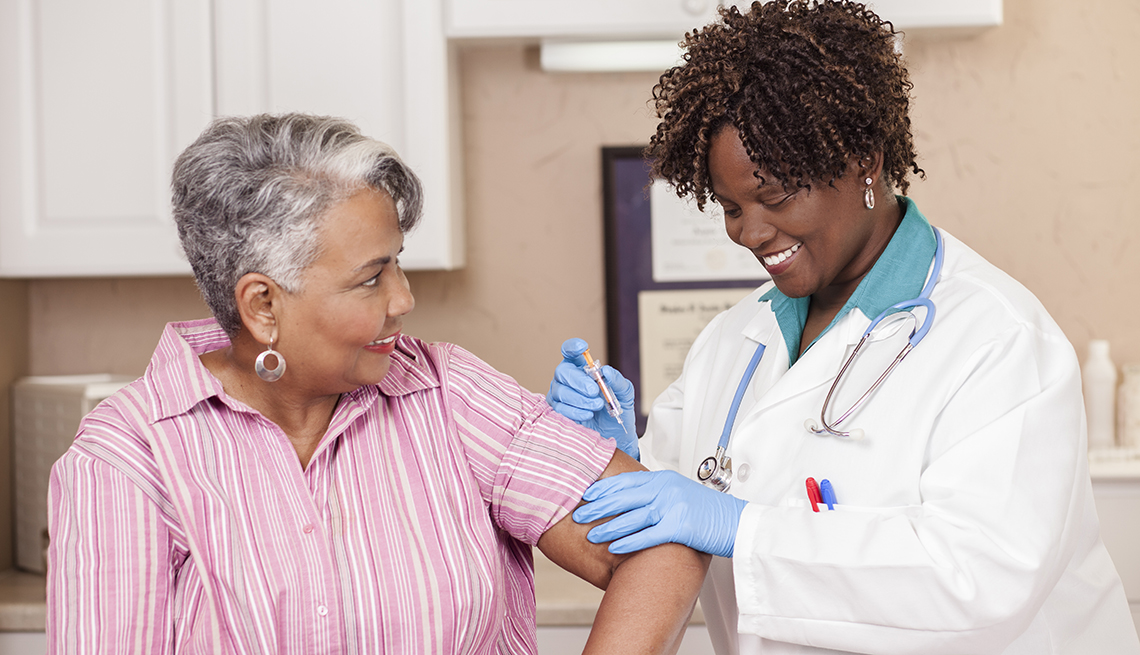 A woman gets a flu shot from a doctor