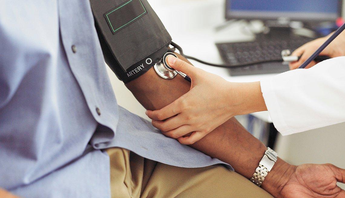 Doctor toma la presión arterial de su paciente