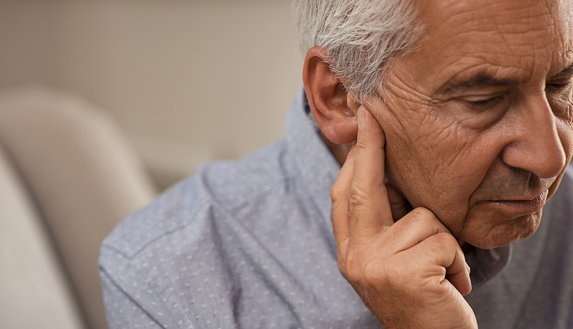 A side view of a man sitting on a couch with his fingers near his ear suffering from apparent hearing loss