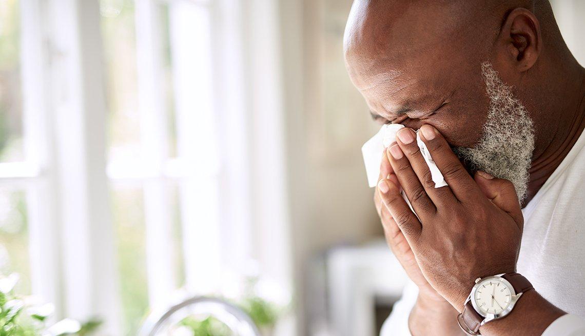 Un hombre sopla su nariz con un un pañuelo