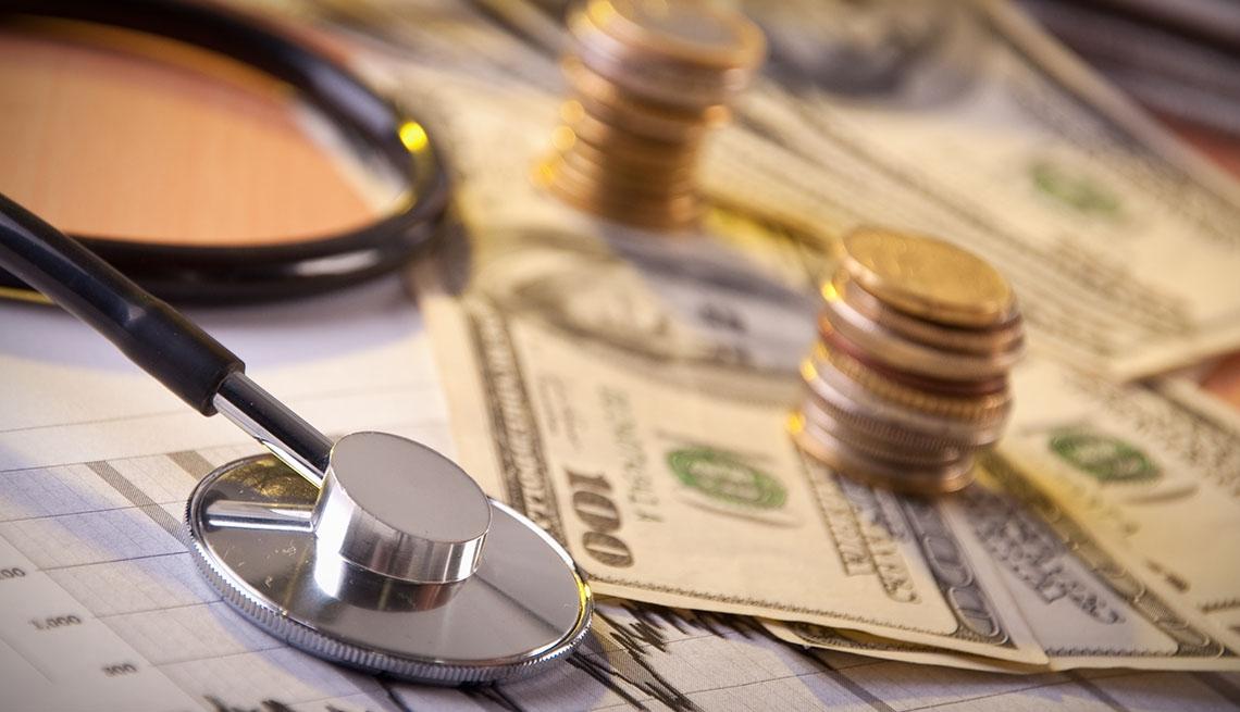 Monedas, dólares y un estetoscopio