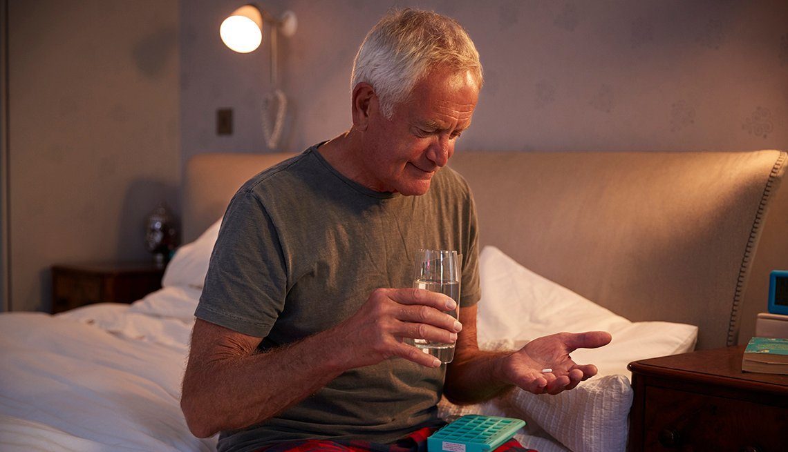 Un hombre toma sus medicamentos sentado en su cama