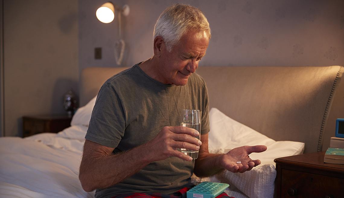 A man sitting on his bed at home holding a glass of water ready to take his medication